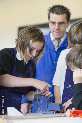 Teacher and students using vice in school workshop