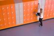 Girl opening locker in school corridor