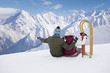Senior couple with sled sitting on snowy mountain top