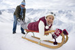 Man pulling legs of smiling woman laying on sled on snowy mountain top