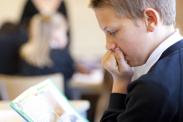 Close up of boy reading in classroom