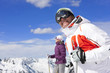 Couple wearing ski goggles and holding ski poles on snowy mountain