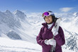Portrait of smiling senior woman with skis on snowy mountain