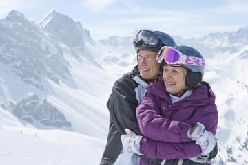 Smiling senior couple hugging on snowy mountain