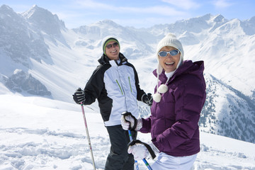 Portrait of smiling senior couple wearing sunglasses and holding ski poles on snowy mountain