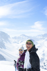 Portrait of laughing senior couple wearing sunglasses and holding ski poles on snowy mountain