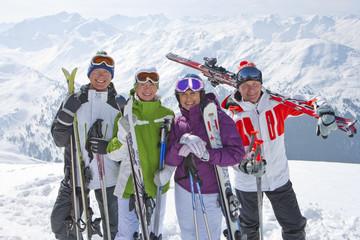 Portrait of smiling senior couples with skis on snowy mountain