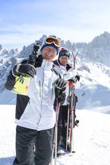 Portrait of smiling senior men with skis on snowy mountain