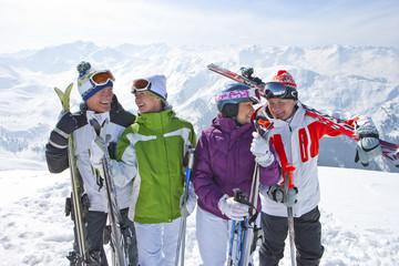 Smiling senior couples with skis on snowy mountain