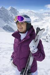 Smiling senior woman holding skis on snowy mountain