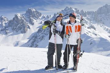 Smiling senior men with skis on snowy mountain