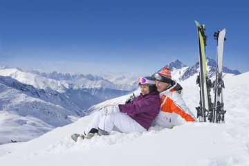 Senior couple with skis sitting on snowy mountain
