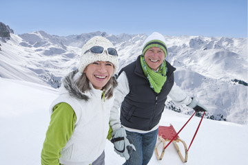 Portrait of smiling senior couple with sled holding hands on snowy mountain