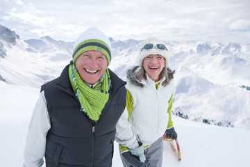 Portrait of smiling couple holding hands on snowy mountain