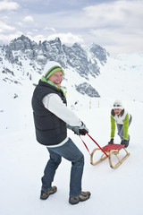 Portrait of smiling couple with sled on snowy mountain