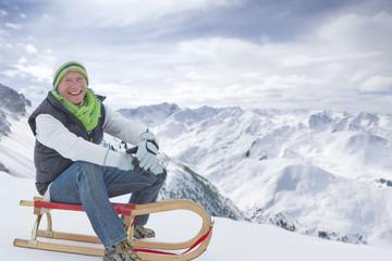Portrait of smiling senior man sitting on sled on snowy mountain