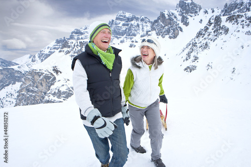 Laughing couple with sled on snowy mountain
