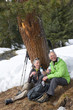 Portrait of happy couple with backpacks drinking water below tree in snowy woods