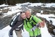 Couple with backpacks and ski poles taking self-portrait near snowy stream