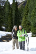 Smiling couple with ski poles and map in snowy woods