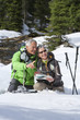 Couple with ski poles, map and compass pointing in snowy woods