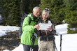 Couple with ski poles looking at map and compass in snowy woods