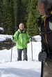 Smiling couple with ski poles trekking in snowy woods