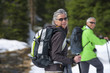 Portrait of smiling couple with ski poles and backpacks trekking in snowy woods