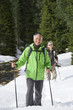 Portrait of smiling couple with ski poles trekking in snowy woods