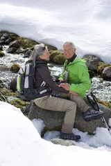 Portrait of smiling couple with backpack drinking coffee and sitting on rock near stream in snow