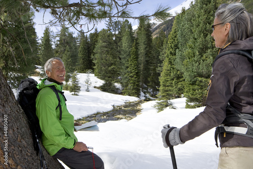 Smiling couple leaning on tree in snowy woods
