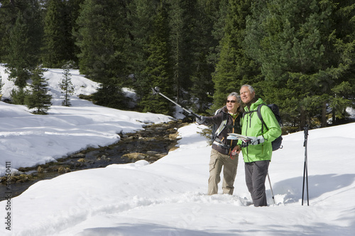 Couple with ski poles and map pointing in snowy woods