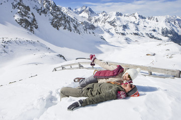 Laughing senior couple laying in snow on mountain