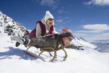 Enthusiastic senior couple sledding on snowy mountain
