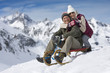 Portrait of smiling senior couple sledding on snowy mountain