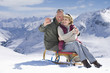 Senior couple on sled taking self-portrait with digital camera on snowy mountain