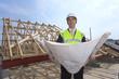Architect holding blueprints at construction site