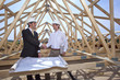 Architects with blueprints handshaking at construction site