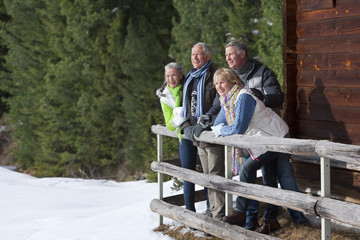 Smiling senior couples leaning on fence outside cabin in snowy woods