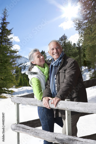 Smiling couple leaning on fence in snowy woods