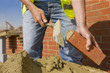 Close up of bricklayer applying mortar to brick with trowel