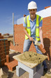 Portrait of bricklayer applying mortar to brick with trowel