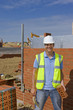 Portrait of confident bricklayer holding brick and trowel in front of wall