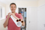 Portrait of man holding copper pipes in front of boiler in closet