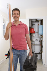 Portrait of smiling handyman with copper pipes and toolbox in front of boiler in closet