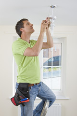 Electrician installing overhead light with compact fluorescent light bulb