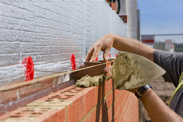 Bricklayer laying brick wall