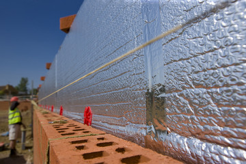 Insulation along brick wall with bricklayer in background