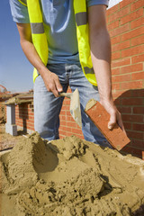 Bricklayer applying mortar to brick with trowel