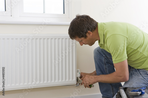 Handyman fixing radiator
